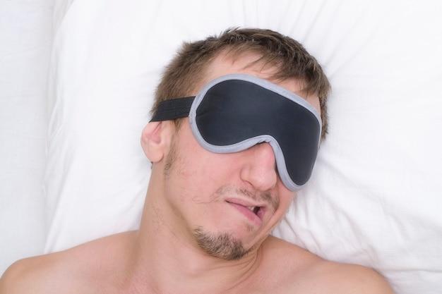 Человек отдыхает в маске для сна. щетина на его лице. усталый человек