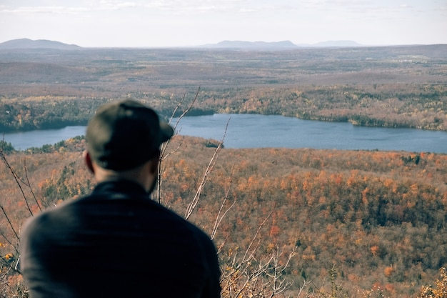 Man resting on a mountain with a beautiful view of river and plains