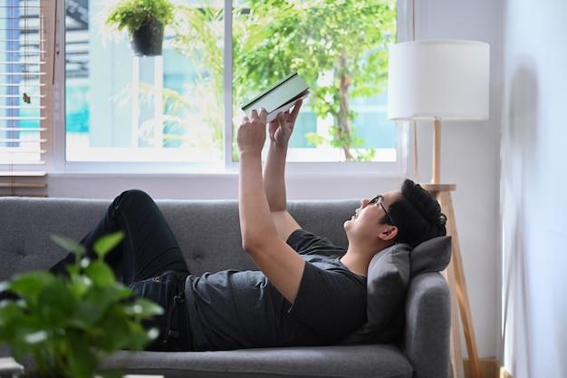 Человек отдыхает на удобном диване и читает книгу.