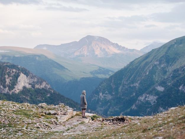 山の中で自然に休んでいる男は、観光の新鮮な空気緑の草を旅行します。高品質の写真