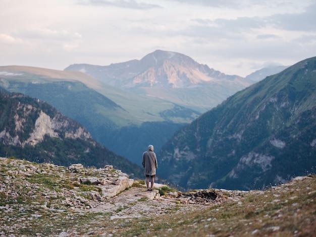 山の中で自然に休んでいる男は、観光の新鮮な空気緑の草を旅行します。