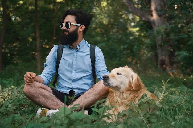 Человек отдыхает на траве, сидя со скрещенными ногами со своей собакой