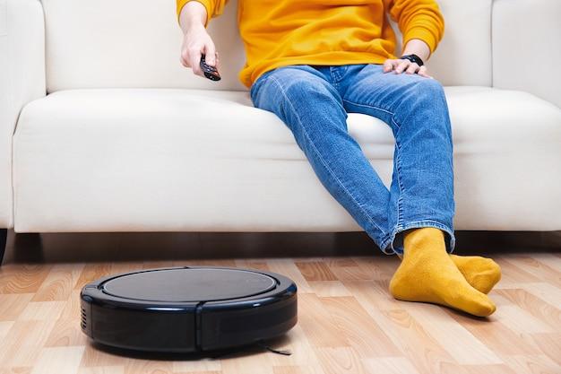 ロボット掃除機が居間とほこりを掃除している間、男はソファで休んでいます。あなた自身のための概念時間。リモコンで掃除機を制御する男。
