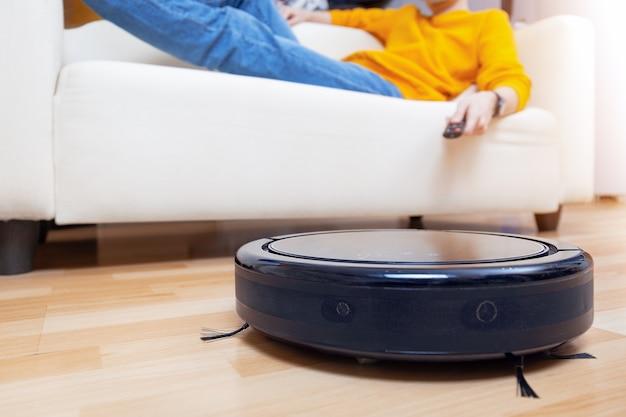 로봇 청소기가 거실과 먼지를 청소하는 동안 소파에서 쉬고 있는 남자. 자신을 위한 개념 시간. 원격 제어로 진공 청소기를 제어하는 남자.