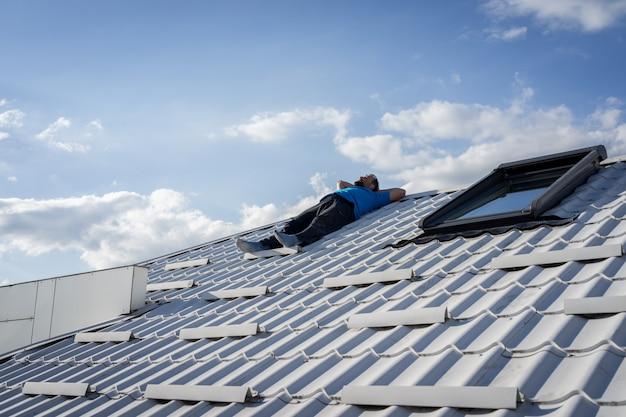 집 지붕 위에 휴식하는 남자