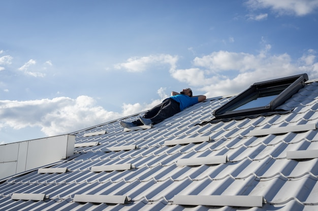 Man resting on the top of house roof