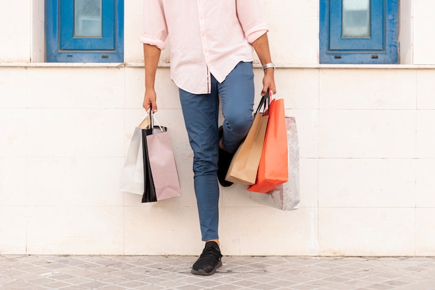Man resting on the wall while holding shopping bags