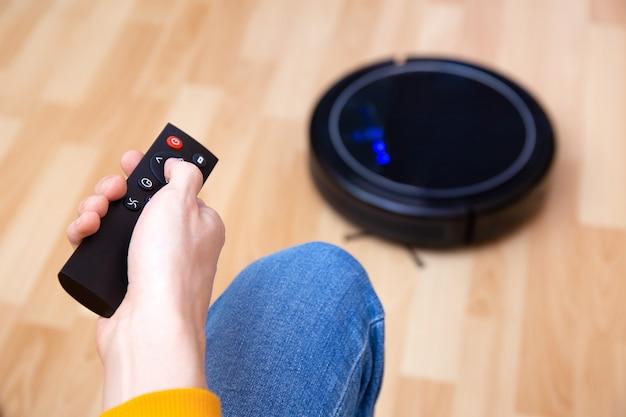로봇 진공 청소기가 집안일을하는 동안 휴식하는 남자, 집에서 깨끗한 작업