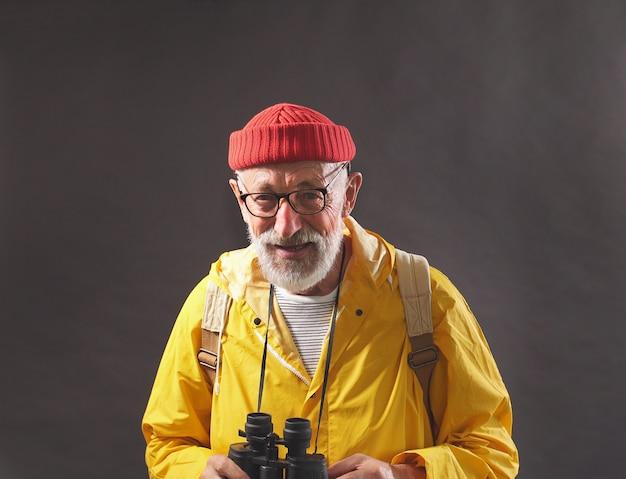 Мужчина на пенсии, старик ведет активный образ жизни, любит путешествовать и всегда берет с собой бинокль, изолированная стена