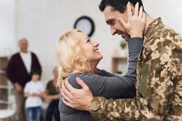 The man returned from the war and his mother meets him.