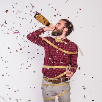 Man in ribbon drinking champagne from bottle