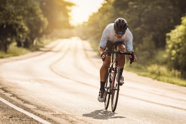 남자는 태양 세트에서 자전거를 타고