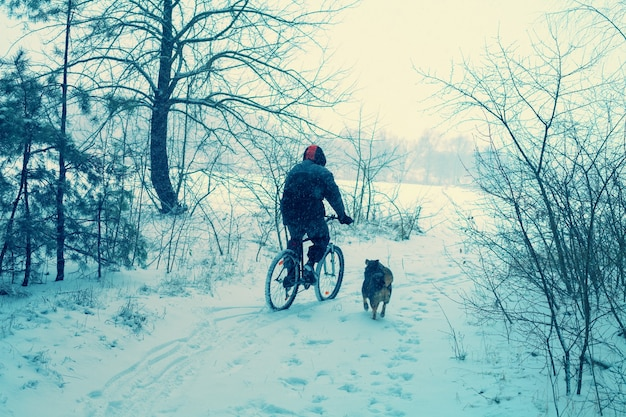 Man ride bicycle in snowy winter. dog running nearby