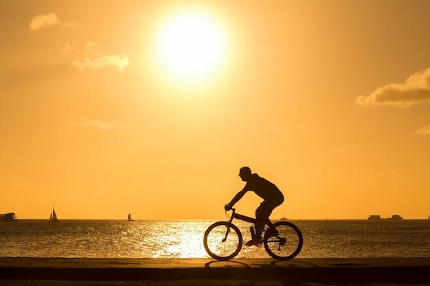 男は日没に対して海のそばで屋外で自転車に乗る。シルエット。
