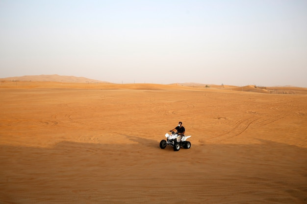 Man ride buggy quad at desert sand wear face mask during quarantine