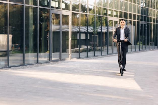 Мужчина едет на электросамокате по дороге - современный способ передвижения красивого мужчину в костюме