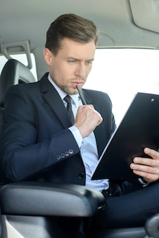 A man rides in the car and something looks in the tablet.