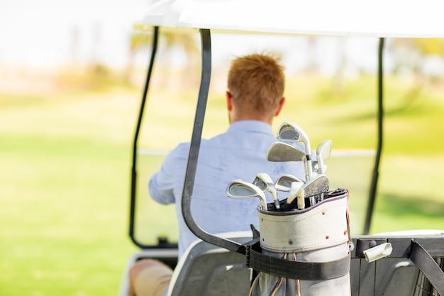 A man rides a golf course on a golf cart.