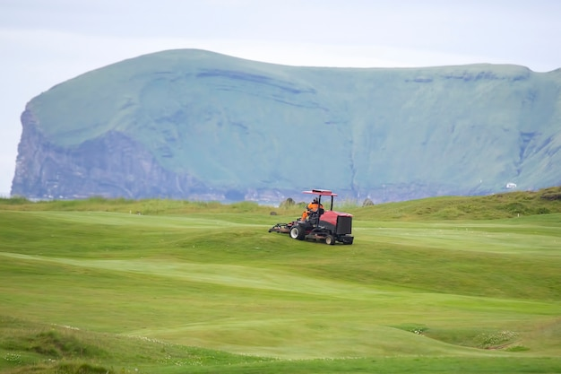 남자는 골프 코스의 잔디를 청소하기 위해 특수 기계를 타고