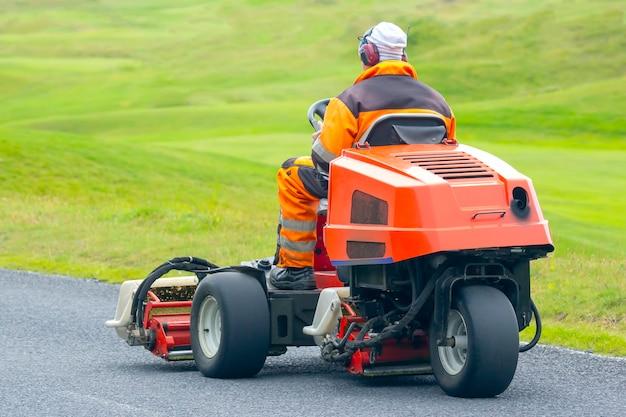 남자는 골프 코스의 잔디를 청소하기 위해 특수 기계를 타고 프리미엄 사진
