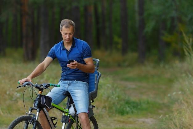 Человек катается на велосипеде в сосновом лесу и смотрит в телефон, спортивный досуг.
