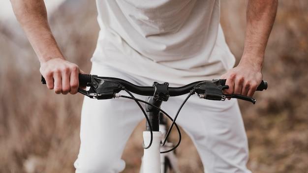 Человек, едущий на велосипеде в белой одежде
