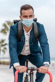 의료 마스크를 착용하는 동안 자전거를 타는 남자