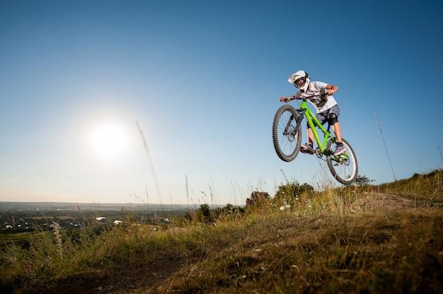 Человек катается на горном велосипеде и прыгает с горы