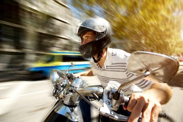 ぼんやりした背景でスピードで道路にスクーターを乗っている男。