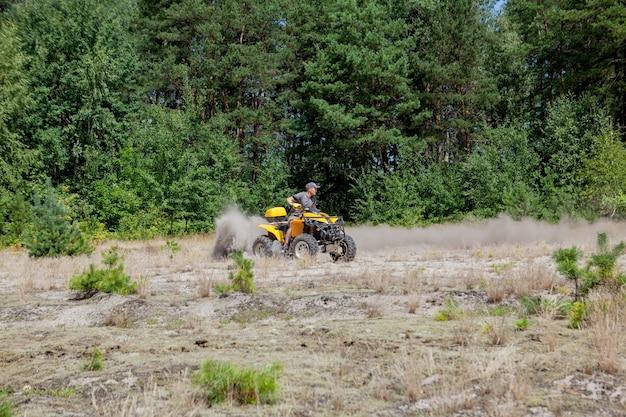 Человек езда желтый квадроцикл вездеход на песчаном лесу. экстремальное спортивное движение, приключения, туристическая достопримечательность.