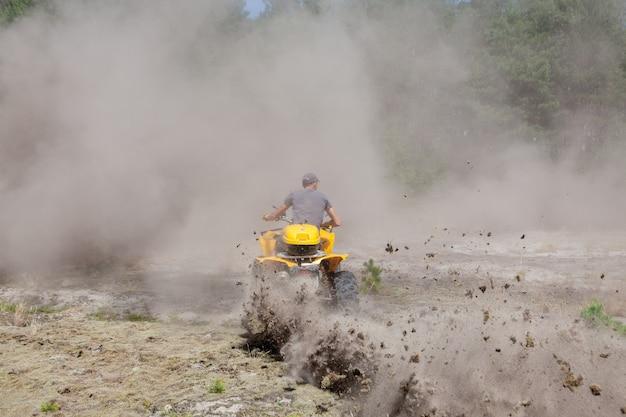 Человек, едущий на желтом квадроцикле вездеход на песчаном лесу.