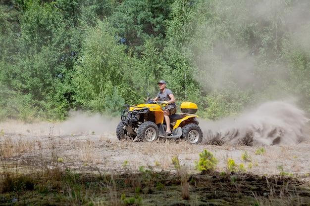 砂の森で黄色いクワッドatv全地形対応車に乗る男