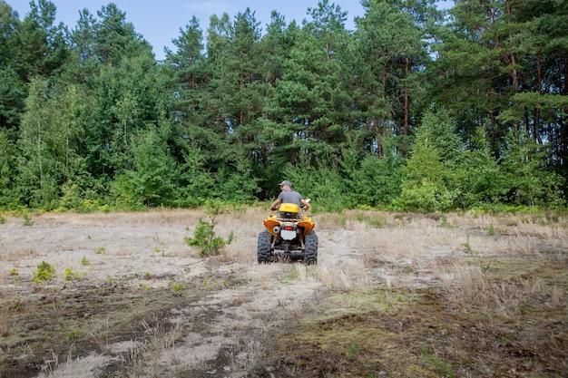 砂の森で黄色いクワッドatv全地形対応車に乗る男。