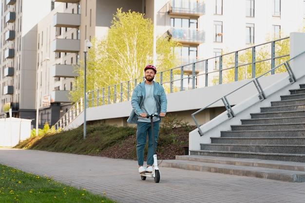 街で環境にやさしいスクーターに乗る男