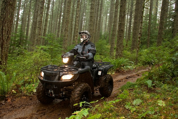 Человек верхом на квадроциклах через лес