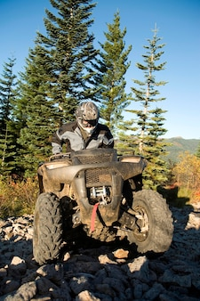 Man riding atv up rocky hill