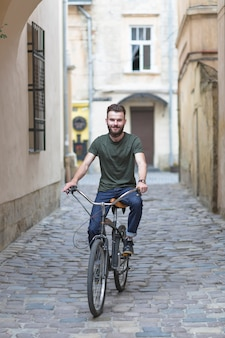 Man riding bicycle on cobble stoned street