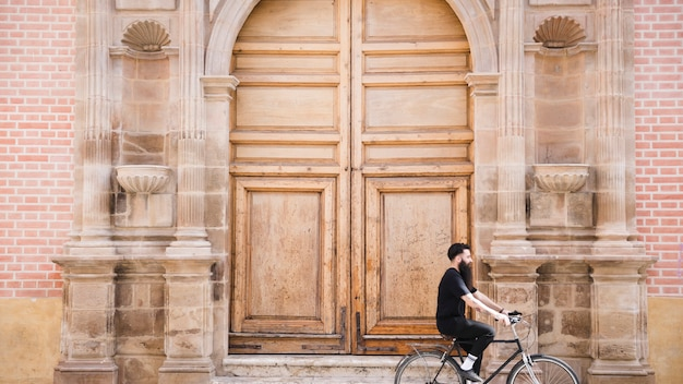 A man riding the bicycle in front of an antique closed door
