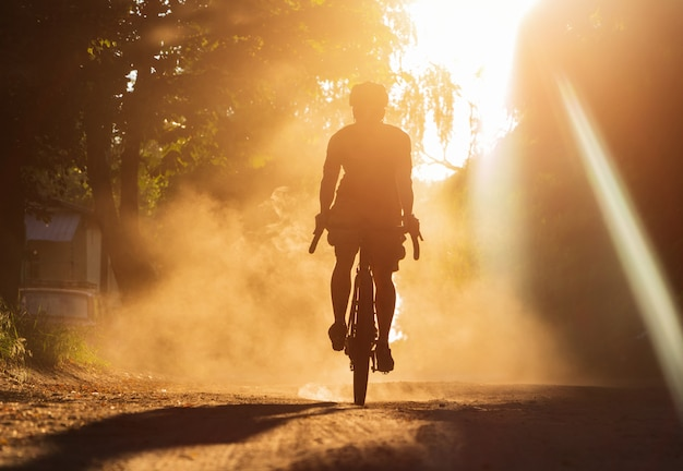 A man riding a bicycle on a gravel road at sunset. a silhouette of a cyclist on a gravel bike in a cloud of dust.