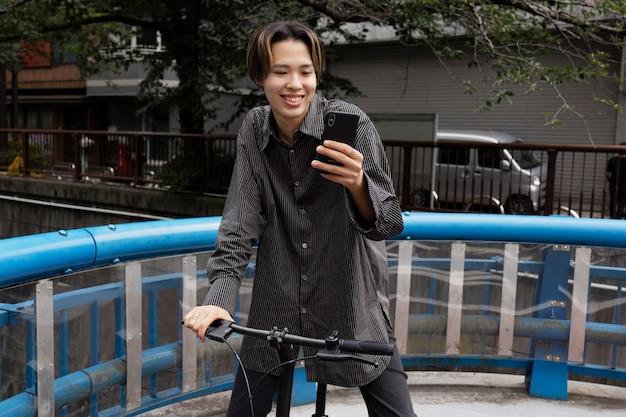 Человек катается на велосипеде в городе и делает селфи со смартфоном