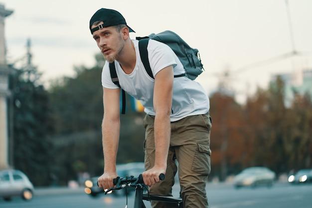 Человек езда на велосипеде в городском городе, держась за руки на руле