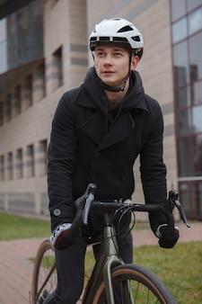 ヘルメットをかぶって、街で自転車に乗る男