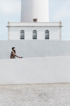 Man riding the bicycle near the white lighthouse