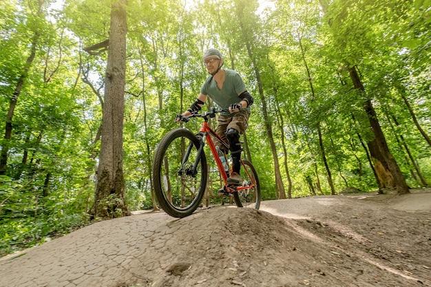 높은 나무의 그림자에서 숲 도로에 자전거를 타는 사람