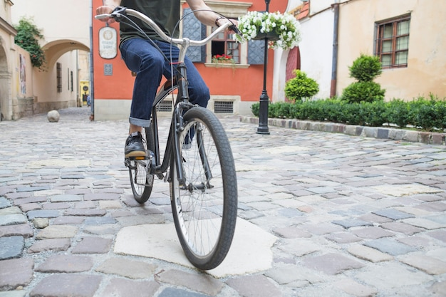 Man riding bicycle on stone pavement