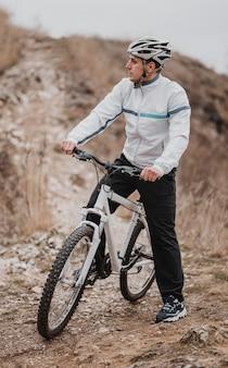 Uomo che guida una bicicletta in una giornata fredda e guarda lontano