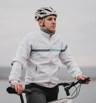 Uomo in sella a una bicicletta in una giornata fredda