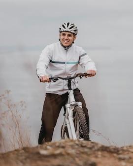 Uomo in sella a una bicicletta in una giornata fredda Foto Gratuite