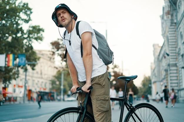 Uomo in sella a una bicicletta in una vecchia città europea all'aperto