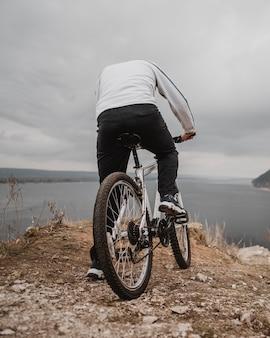 Uomo che guida una bicicletta all'aperto